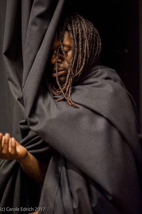 a man offers his hand wrapped in a black curtain as part of the performance piece Obibini